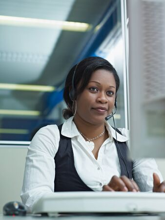 female african american customer service representative talking on the phone and typing on pc. Vertical shape, front view photo