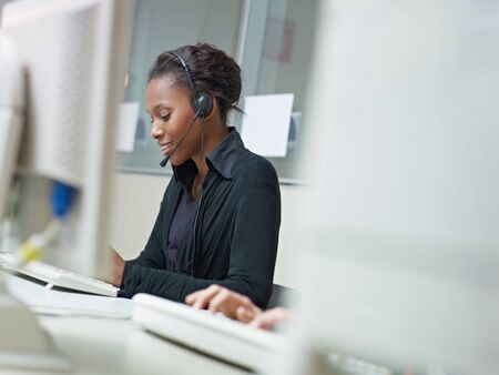 female african american customer service representative talking on the phone and typing on pc. Horizontal shape, side view, copy space photo