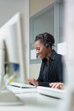 customer service representative: female african american customer service representative talking on the phone and typing on pc. Verical shape, side view, copy space