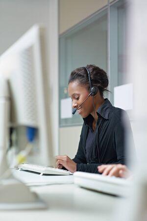 servicio al cliente: representante de servicio de mujeres al cliente Africano Americano, hablando por tel�fono y escribiendo en pc. Copiar de forma vertical, vista lateral, espacio