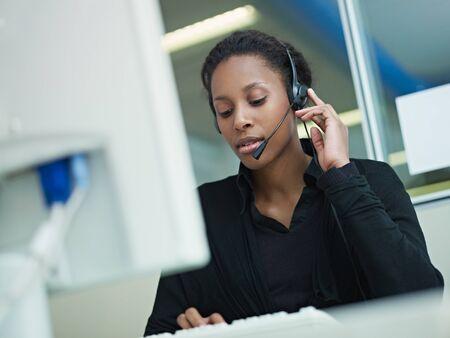 servicio al cliente: representante de servicio de cliente Africano Americano femenina con auriculares escribiendo en equipo. Forma horizontal, la vista frontal, la cintura para arriba