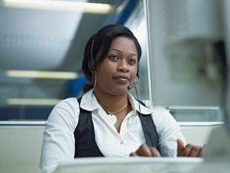 operators: female african american customer service representative talking on the phone and typing on pc. Horizontal shape, front view