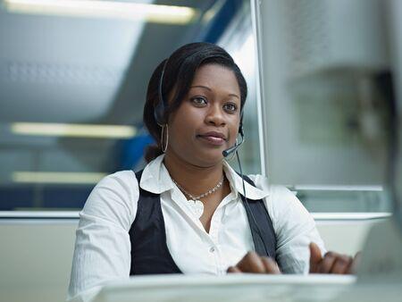 servicio al cliente: representante de servicio de mujeres al cliente Africano Americano, hablando por tel�fono y escribiendo en pc. Forma horizontal, vista frontal