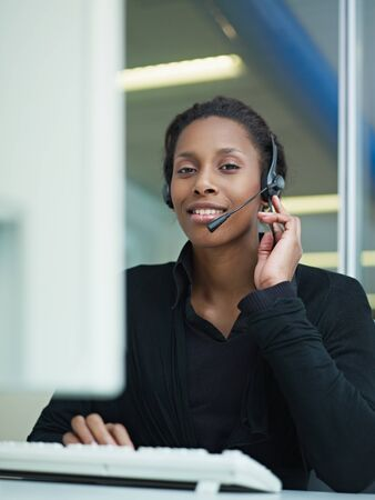 computer centre: female african american customer service representative with headset looking at camera and smiling. Verical shape, front view, waist up Stock Photo