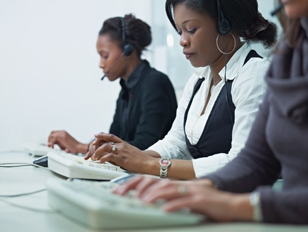 representative: multiethnic group of female customer service representatives talking on the phone and typing on computer keyboard. Horizontal shape, side view, copy space
