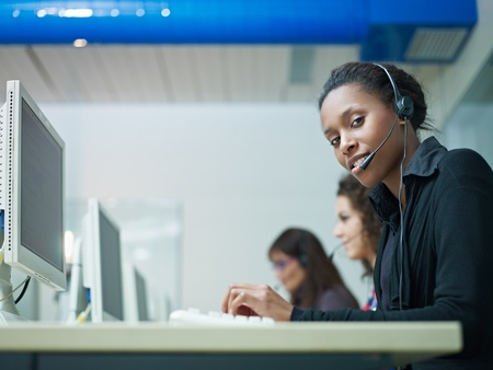 multiethnic group of female customer service representatives talking on the phone, with african woman looking at camera. Horizontal shape, side view, copy space photo