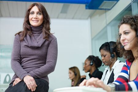 confident businesswoman with multiethnic group of female customer service representatives talking on the phone. Horizontal shape, waist up, front view photo