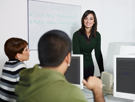 computer classes: Computer class with caucasian female teacher talking to hispanic student. Horizontal shape, focus on background