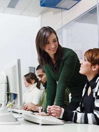 Computer class with caucasian female teacher helping student. Vertical shape, side view, waist up photo