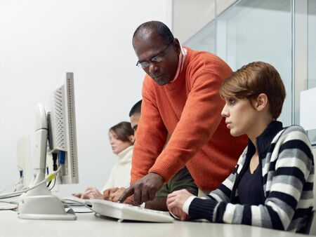 Computer class with indian male teacher helping female student. Horizontal shape, side view, waist up, copy space photo