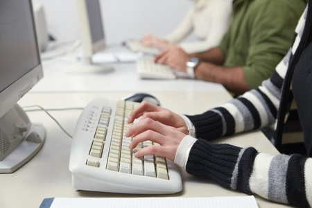 Closeup of caucasian female student typing on keyboard in computer lab. Horizontal shape, side view photo