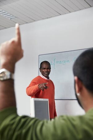 Computer lab with hispanic student asking question with hand raised to mature indian teacher. Vertical shape, focus on background, copy space photo