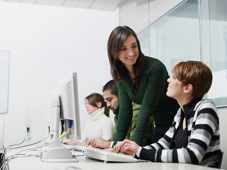 Computer lab with caucasian female teacher helping student. Horizontal shape, side view, waist up, copy space photo