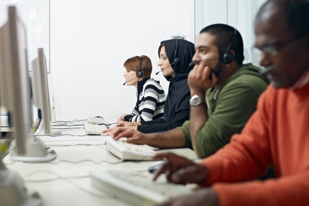 training group: Multiethnic computer class with indian, middle eastern, hispanic and caucasian people training with pc. Horizontal shape, side view, waist up Stock Photo