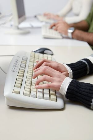 Closeup of caucasian female student typing on keyboard in computer lab. Vertical shape, side view photo