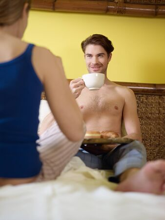 caucasian heterosexual couple eating croissant and drinking coffee in bed. Vertical shape, rear view, focus on background photo
