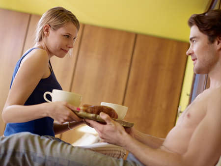 caucasian woman carrying breakfast to her boyfriend in bed. Horizontal shape, side view photo