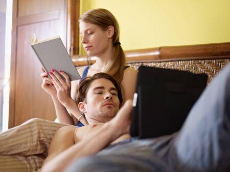 pijama: cauc�sica pareja heterosexual que se divierten en cama con libro y tablet pc. Forma horizontal, la longitud de tres cuartos, la vista lateral