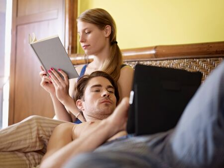 three quarter length: caucasian heterosexual couple having fun on bed with book and tablet pc. Horizontal shape, three quarter length, side view