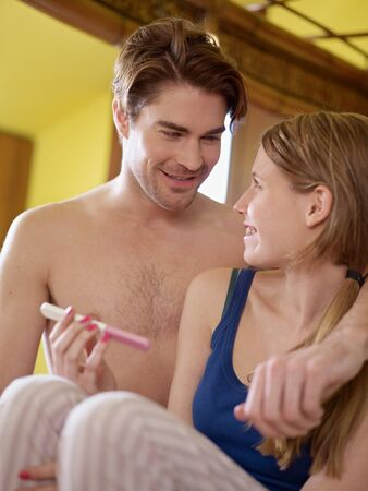 young caucasian woman in tanktop showing positive pregnancy test to her husband and smiling. Vertical shape, three quarter length, front view photo