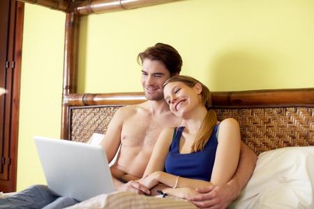 three quarter length: caucasian heterosexual couple watching movie on laptop computer in bedroom. Horizontal shape, three quarter length, side view