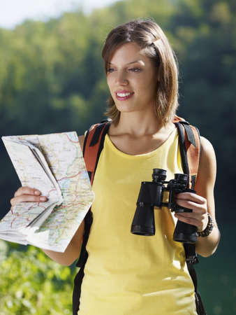 bird watcher: young caucasian female hiker reading map and holding binoculars. Vertical shape, waist up, front view