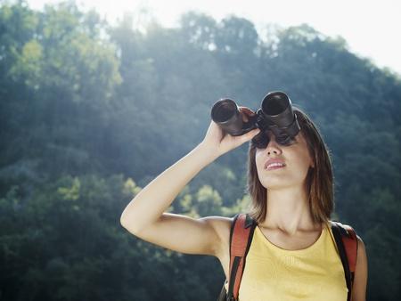personas mirando: jóvenes excursionista mujer caucásica viendo a través de binoculares. Forma horizontal, vista frontal, cabeza y hombros, espacio de copia