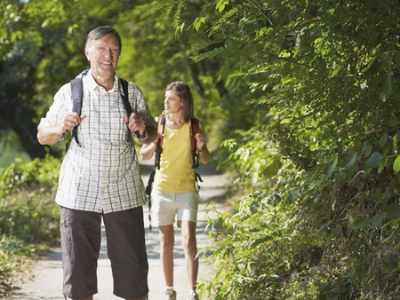 senior man and young woman walking with backpack in wood, looking at camera and smiling. Horizontal shape, front view, copy space photo