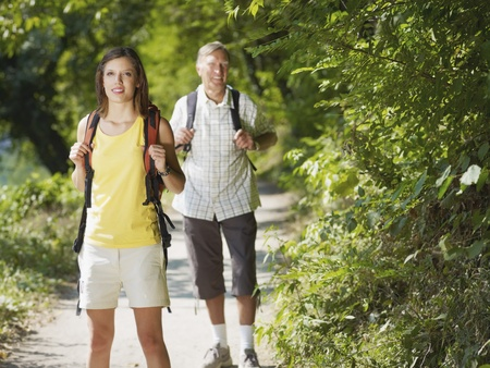 senior man and young woman walking with backpack in wood, looking at camera and smiling. Horizontal shape, front view, copy space Stock Photo - 8681742