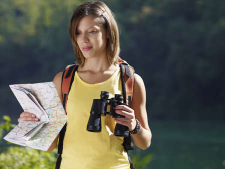 bird watcher: young caucasian female hiker reading map and holding binoculars. Horizontal shape, waist up, copy space Stock Photo