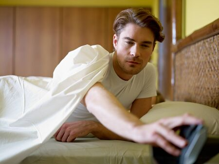 get tired: caucasian adult man in bed snoozing alarm clock and waking up. Horizontal shape, waist up, front view