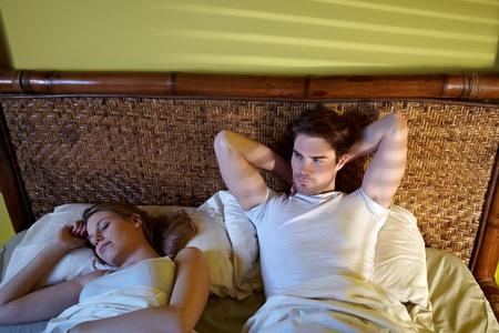 insomnio: cauc�sica pareja heterosexual en cama, hombre que sufren de insomnio. Copiar de forma horizontal, gran �ngulo de visi�n, espacio
