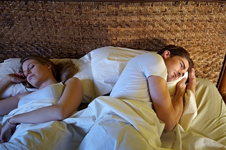 caucasian heterosexual couple in bed, man suffering from insomnia. Horizontal shape, high angle view Stock Photo - 8843064