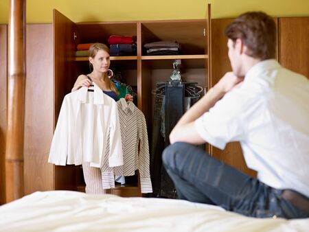 caucasian couple getting dressed in the morning, with woman choosing shirt. Horizontal shape, front view, three quarter length photo