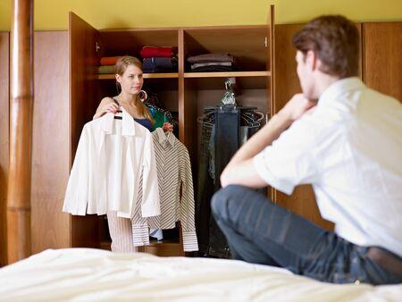 vistiendose: pareja cauc�sica vestirse en la ma�ana, con la mujer elecci�n camisa. Forma horizontal, vista frontal, tres cuartos de longitud