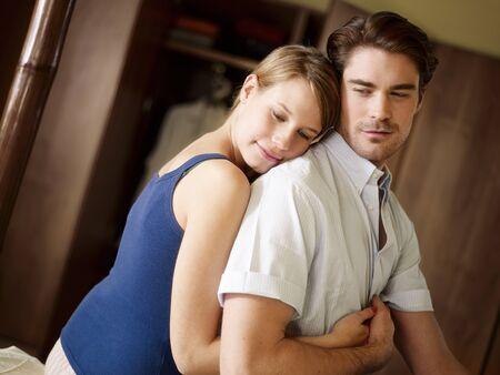 jóvenes de marido y mujer sentada en la cama y abrazos. Forma horizontal, de cintura para arriba, vista lateral Foto de archivo - 8843069