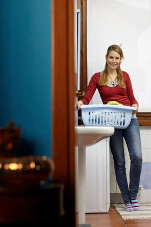 portrait of young adult caucasian woman leaning on washing machine and looking at camera with clothes basket. Vertical shape, front view, copy space Stock Photo - 8843071