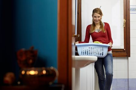 portrait of young adult caucasian woman leaning on washing machine and looking at camera with clothes basket. Horizontal shape, front view, copy space photo