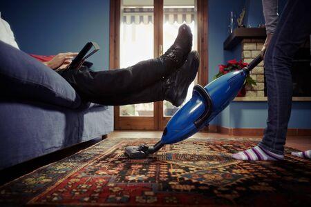 perezoso: pareja heterosexual del C�ucaso, con mujer haciendo las tareas usando la aspiradora de alfombra y perezoso hombre en sof� con tablet pc. Forma horizontal, vista de �ngulo bajo