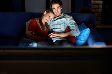 viewing: giovane coppia eterosessuale, abbracciando sul divano e guardare film in tv a casa. Forma orizzontale, vista frontale, copy space
