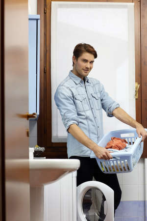 portrait of adult caucasian man leaning on washing machine and looking at camera with clothes basket. Vertical shape, side view photo