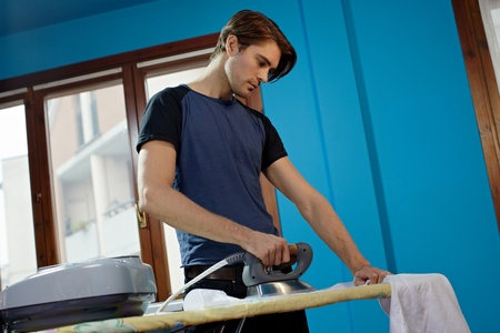 portrait of caucasian adult man ironing white shirt at home. Horizontal shape, low angle view, side view photo