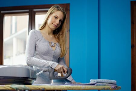 portrait of caucasian adult woman ironing clothes at home. Horizontal shape, front view, copy space photo
