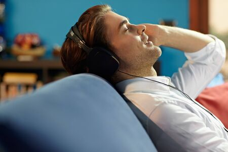 caucasian adult man relaxing on sofa with headphones. Horizontal shape, side view, head and shoulders, copy space photo
