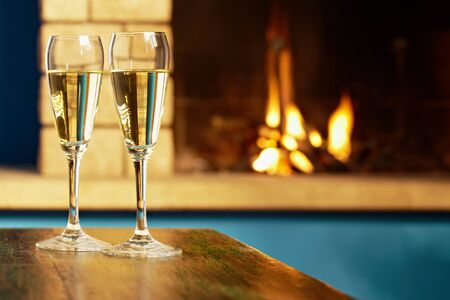 closeup of two wine glasses with champagne on table and fireplace in background. Horizontal shape photo