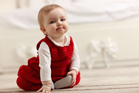 portrait of 6 months female child sitting on floor in red clothes and looking at camera. Horizontal shape, front view, copy space Stock Photo - 8843292