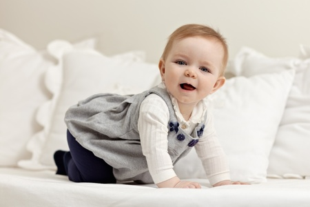 walking baby: portrait of 6 months female child playing on bed and looking at camera. Horizontal shape, side view, full length