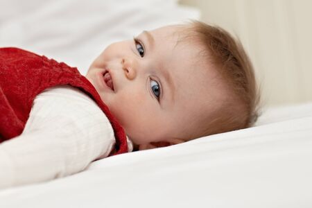 portrait of 6 months female child lying on back on bed and looking at camera. Horizontal shape, side view, copy space photo