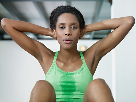 breathing exercise: young african american woman in green sportswear exercising abdominals in fitness club, looking at camera. Horizontal shape, front view, waist up Stock Photo