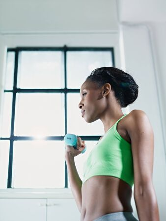 young african american woman in green sportswear doing weight lifting in fitness club. Vertical shape, side view, copy space photo